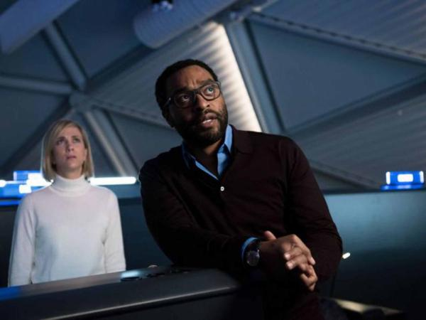 Chiwetel Ejiofor, looked on by Kirsten Wiig, playing it straight for once.
